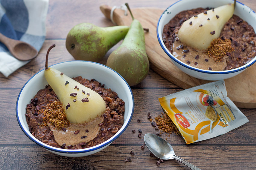 two bowls healthy chocolate porridge with poached pear with Linwoods seeds